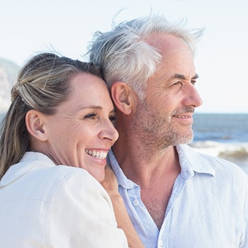 A middle-aged couple stands on the beach and smiles.