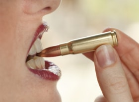 Close up of a woman's mouth biting a bullet to show that this Alexandria dentist can assist with removing metal fillings