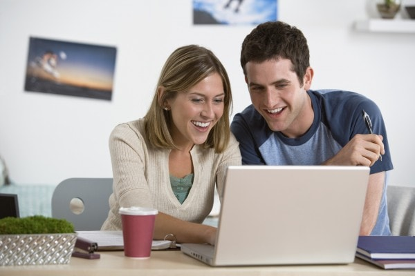 Smiling couple checks out the website of their dentist for Fairfax VA