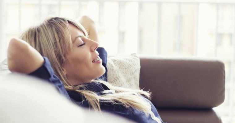 A blond haired woman relaxing in a comfy chair to show that you can feel relaxed and calm at your dental appointment with sedation dentistry options