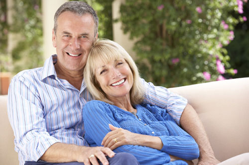 Mature couple smiling from implant-retained dentures