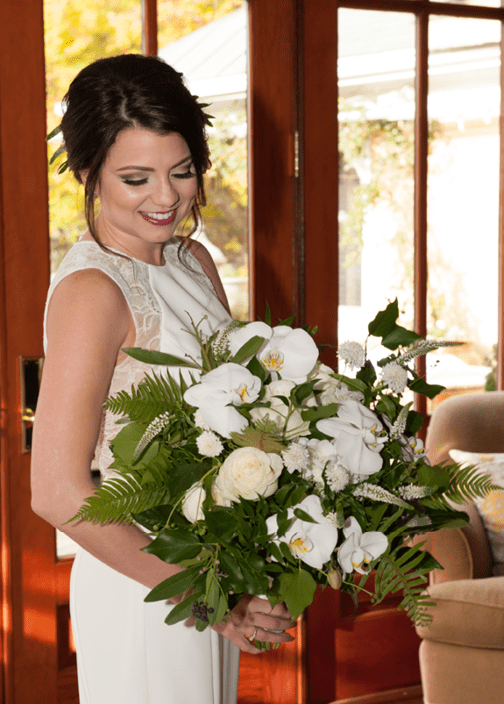 Smiling bride looking at her wedding flowers. She loves her bright smile, thanks to KöR Teeth Whitening® with Dr. Alex McMillan