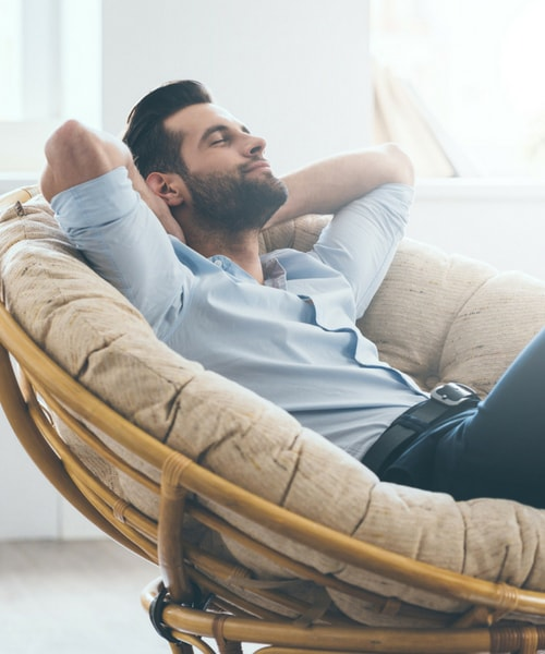 Man relaxed in a comfy chair after oral sedation treatment