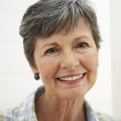 Smiling grey-haired woman with beautiful teeth.